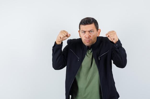 Jovem macho ameaçando com punhos em t-shirt, jaqueta e parecendo com raiva. vista frontal.