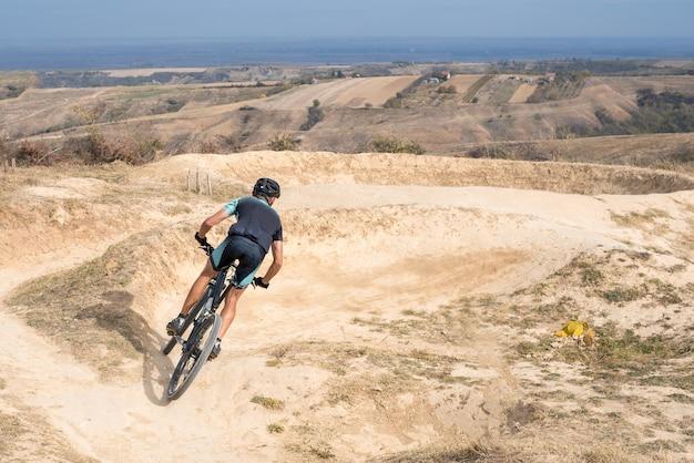 Jovem macho andando de bicicleta em terreno acidentado