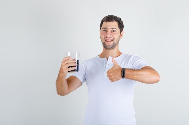 Jovem macho aparecendo o polegar com uma bebida de cola em uma camiseta branca e parecendo feliz