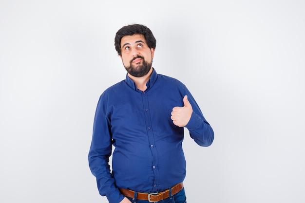 Jovem macho aparecendo o polegar em uma camisa, jeans e olhando pensativo, vista frontal.