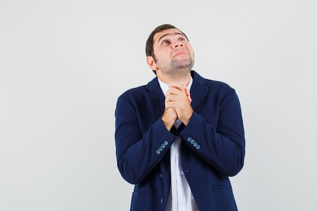 Jovem macho apertando as mãos em gesto de oração na camisa e jaqueta e olhando esperançoso.