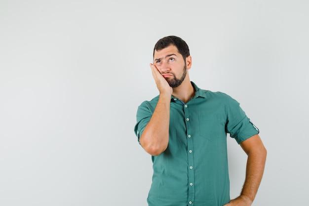 Jovem macho apoiado na palma da mão enquanto olha para longe em uma camisa verde e olhando pensativo, vista frontal. espaço para texto