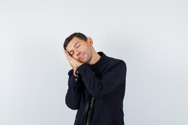 Jovem macho apoiado nas palmas das mãos como travesseiro em uma camiseta, jaqueta e parecendo tranquilo. vista frontal.