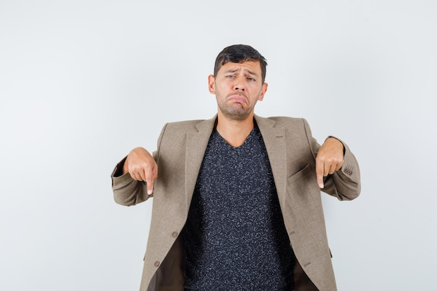 Jovem macho apontando para baixo em uma jaqueta marrom acinzentada, camisa preta e parecendo chateado. vista frontal.