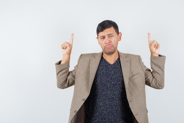Jovem macho apontando para cima com jaqueta marrom acinzentada e parecendo chateado, vista frontal.