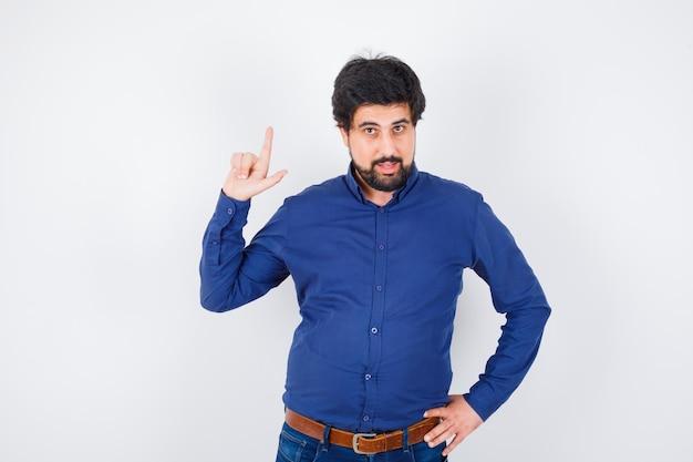 Jovem macho apontando para cima em camisa, jeans e parecendo confiante, vista frontal.