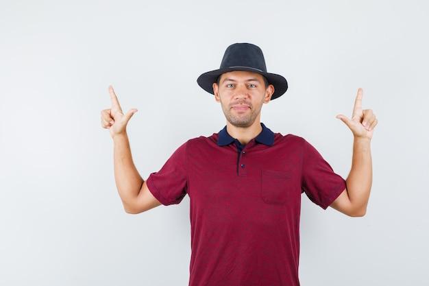 Jovem macho apontando para cima em camisa vermelha, chapéu preto e parecendo confiante, vista frontal.