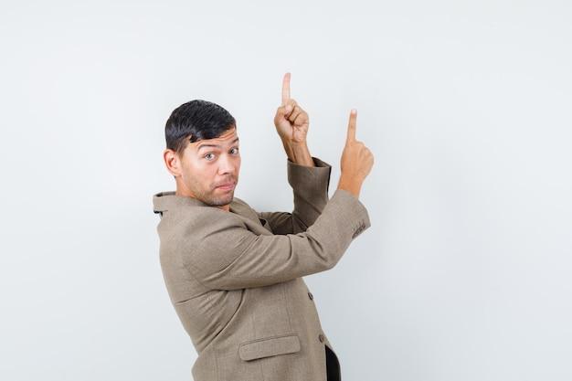 Jovem macho apontando para cima em uma jaqueta marrom acinzentada, camisa preta e olhando com cuidado.