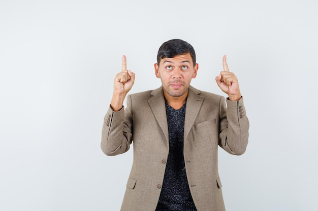 Jovem macho apontando para cima em uma jaqueta marrom acinzentada, camisa preta e parecendo concentrado. vista frontal.