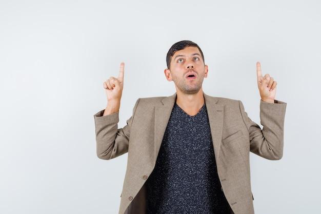 Jovem macho apontando para cima em uma jaqueta marrom acinzentada e olhando com cuidado. vista frontal.