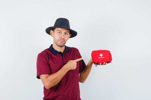 Jovem macho apontando para o kit de ajuda rápida na camisa vermelha, chapéu preto e olhando sério, vista frontal.