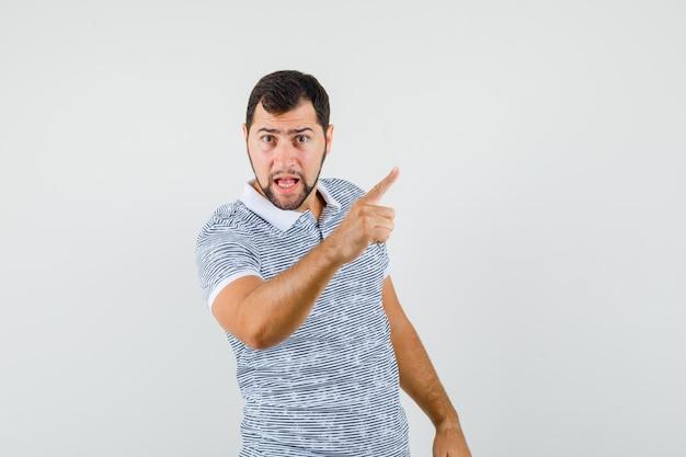 Jovem macho apontando para o lado com o dedo para cima na camiseta e parecendo zangado. vista frontal.