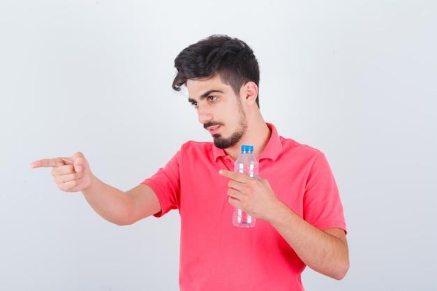 Jovem macho apontando para o lado em t-shirt e olhando focado. vista frontal.