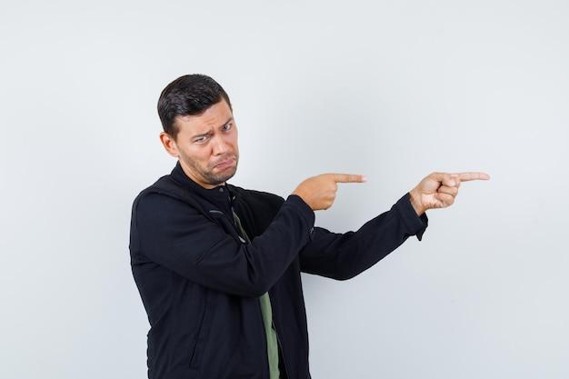 Jovem macho apontando para o lado em t-shirt, jaqueta e parecendo desapontado, vista frontal.