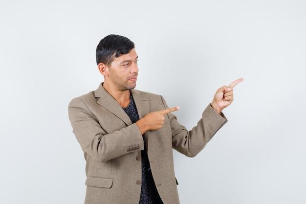 Jovem macho apontando para o lado em uma jaqueta marrom acinzentada, camisa preta e parecendo focado. vista frontal.