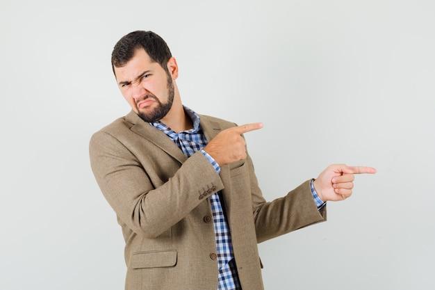 Jovem macho apontando para o lado na camisa, jaqueta e parecendo enojado. vista frontal.