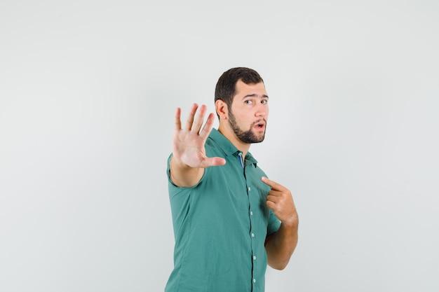 Jovem macho apontando para si mesmo enquanto mostra o gesto de parada na camisa verde e parecendo descontente. vista frontal.