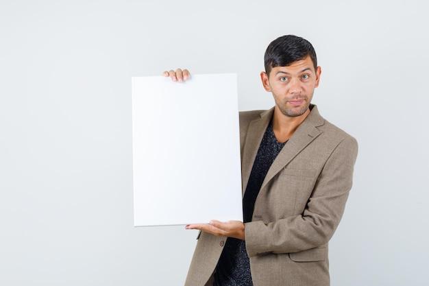 Jovem macho apontando para um papel em branco em uma jaqueta marrom acinzentada e olhando inteligente, vista frontal.