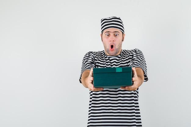 Jovem macho apresentando caixa de presente em t-shirt, chapéu e olhando maravilhado, vista frontal.