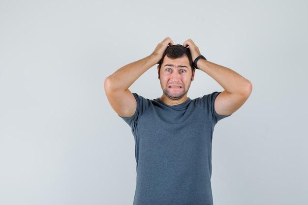 Jovem macho arrancando o cabelo em uma camiseta cinza e parecendo melancólico