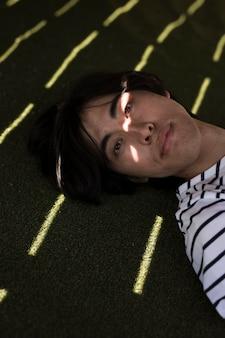 Jovem, macho asiático, olhando câmera, enquanto, mentindo, em, sombra