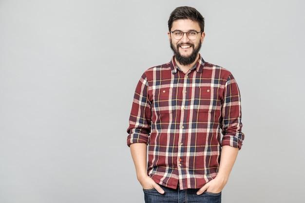 Jovem macho bonito com barba contra fundo cinza