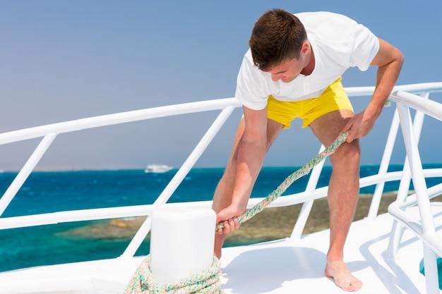 Jovem macho bonito diligentemente conserta corda em um iate em um dia ensolarado de verão, lindo mar no fundo