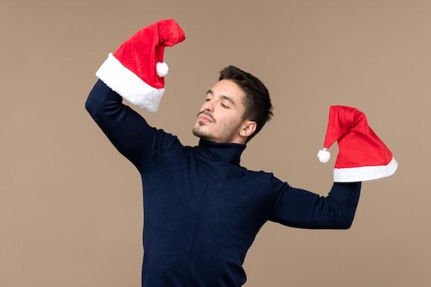 Jovem macho brincando com bonés vermelhos na mesa marrom emoção feriado de natal