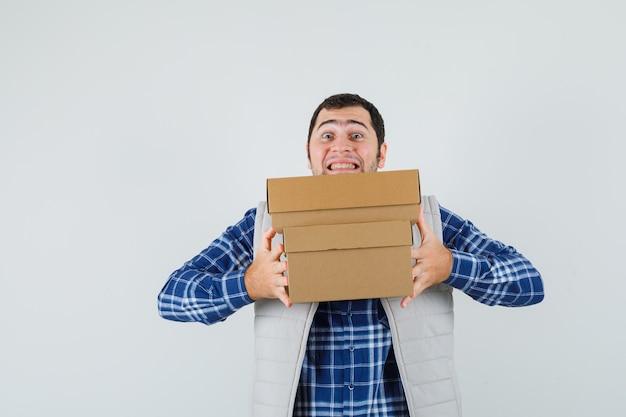 Jovem macho carregando caixas na camisa, jaqueta e olhando alegre, vista frontal.