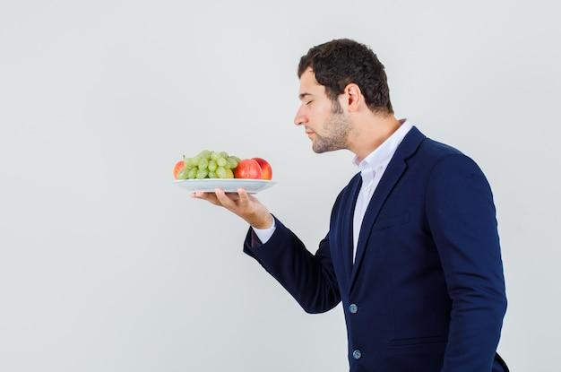 Jovem macho cheirando frutas frescas no prato de terno e parecendo em paz. .