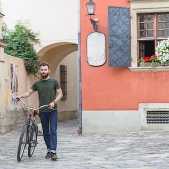 Jovem, macho, ciclista, andar, com, seu, bicicleta, ligado, pavimento pedra