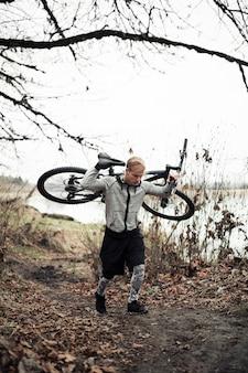 Jovem, macho, ciclista, carregar, seu, montanha, bicicleta