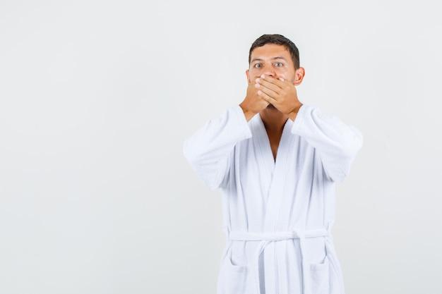 Jovem macho cobrindo a boca com as mãos no roupão branco e parecendo surpreso. vista frontal.