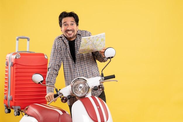 Jovem macho com bicicleta segurando um mapa sorrindo em amarelo