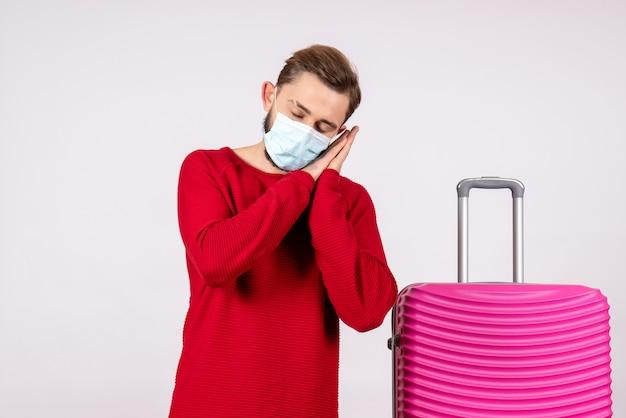 Jovem macho com bolsa rosa na máscara dormindo na parede branca viagem covid- vôo viagem férias emoção vírus
