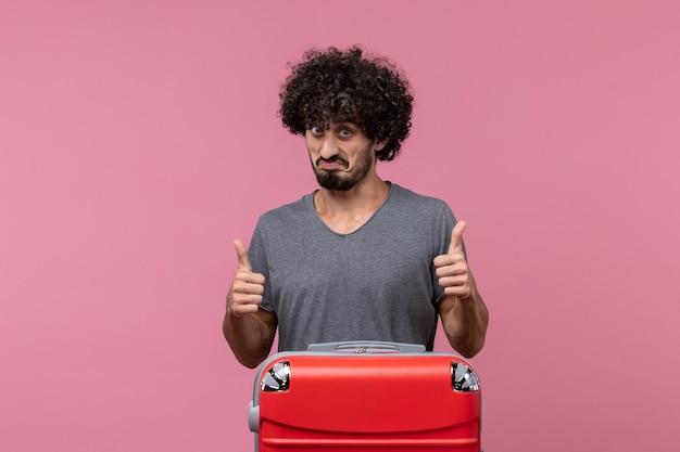 Jovem macho com bolsa vermelha posando no espaço rosa
