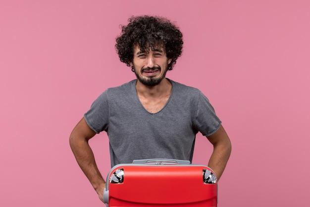 Jovem macho com bolsa vermelha se preparando para uma viagem chorando no espaço rosa claro