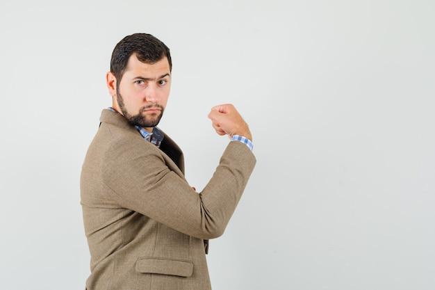 Jovem macho com camisa, jaqueta mostrando seus músculos e parecendo decidido.