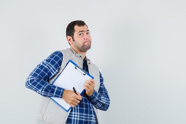 Jovem macho com camisa, jaqueta segurando a prancheta enquanto vai e olha preparado, vista frontal. espaço para texto