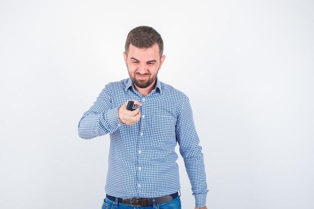 Jovem macho com camisa, jeans, fingindo uma luz mais leve e parecendo confiante, vista frontal.
