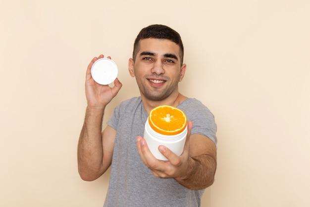 Jovem macho com camiseta cinza segurando uma lata vazia e laranja sorrindo em bege