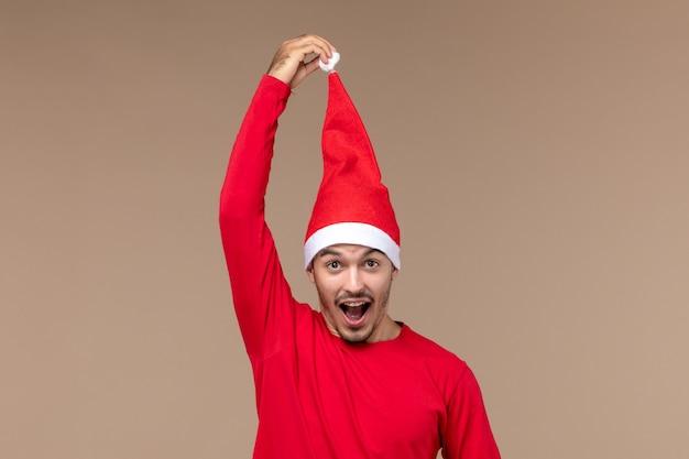 Jovem macho com capa de natal em fundo marrom, feriado natal, emoção