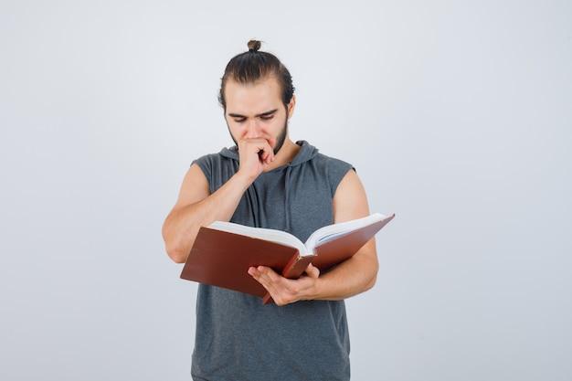 Jovem macho com capuz sem mangas, olhando para o livro, segurando a mão na boca e olhando pensativo, vista frontal.