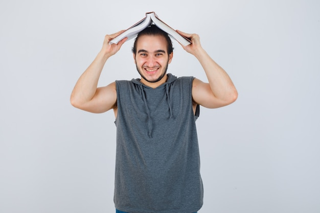Jovem macho com capuz sem mangas segurando o livro aberto na cabeça como telhado de casa e olhando engraçado, vista frontal.