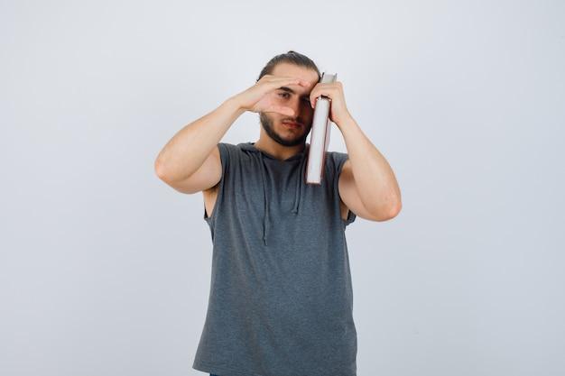 Jovem macho com capuz sem mangas segurando o livro no ombro enquanto mostra a placa do tamanho e olhando sério, vista frontal.