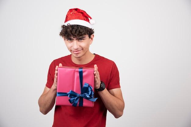 Jovem macho com chapéu de papai noel, posando com caixa de presente.