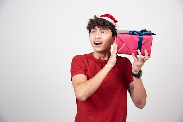 Jovem macho com chapéu de papai noel segurando o presente.