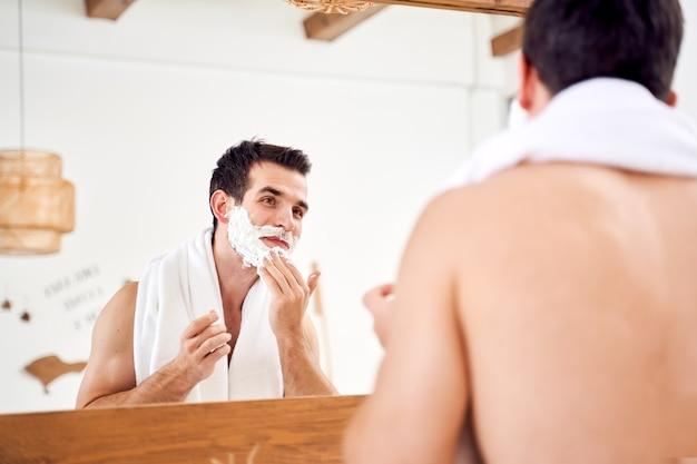 Jovem macho com espuma na barba perto do espelho pela manhã