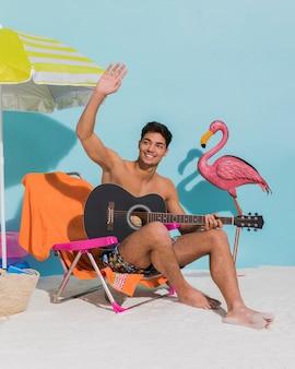 Jovem macho com guitarra acenando com a mão na praia