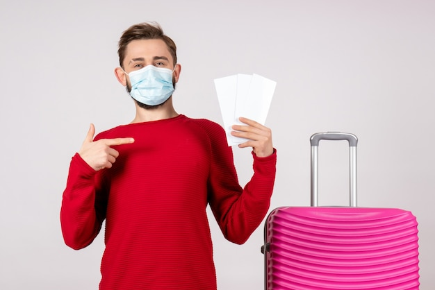 Jovem macho com máscara estéril segurando bilhetes na parede branca covid - vôo viagem férias cor emoção vírus